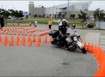 Policininkas laiko motociklo vairavimo egzaminą
