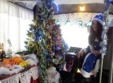 Naujametinis autobusas su Kalėdų seneliu prie vairo ir Snieguole